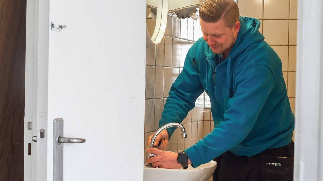 vvs installatør installerer armatur i et nyt badeværelse